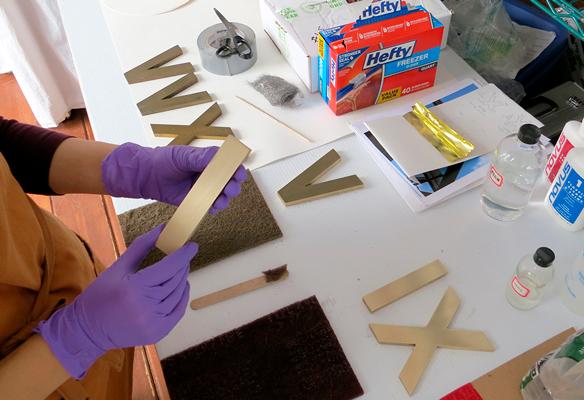 Laura Kubick restoring bronze numerals.